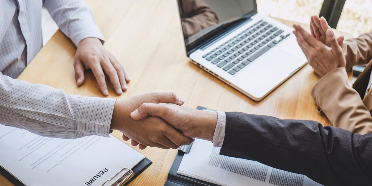 A data analyst job applicant shaking hands with an interviewer
