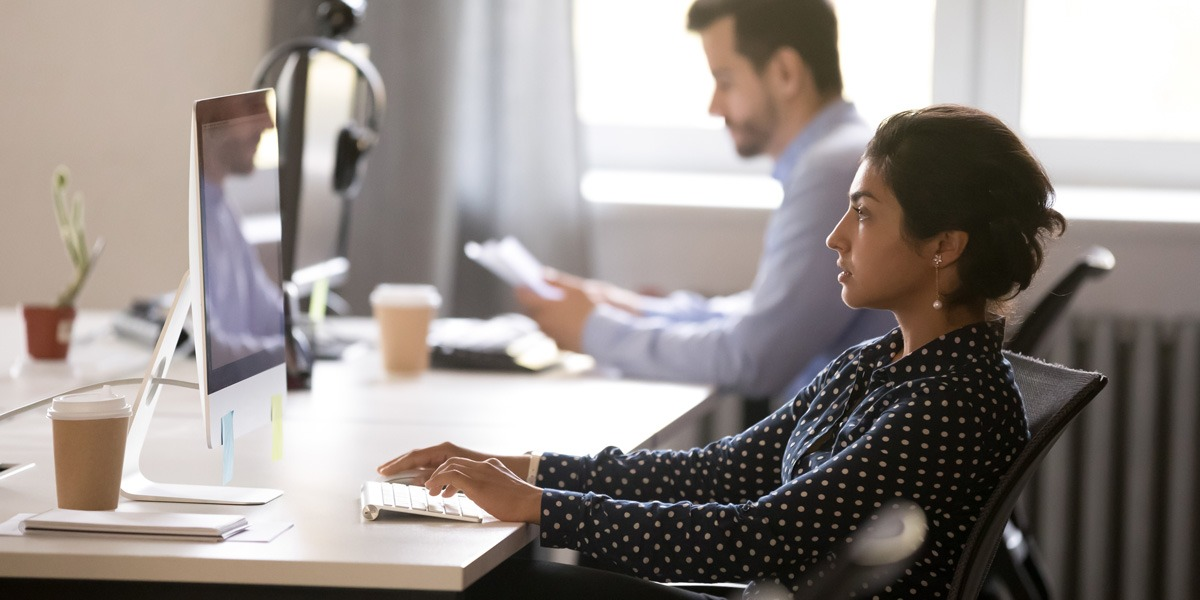 Two data analysts in side profile, working in an office