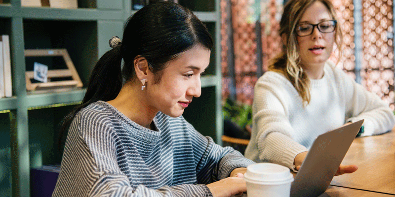 Two designers sitting at a table, looking at the microcopy in their product