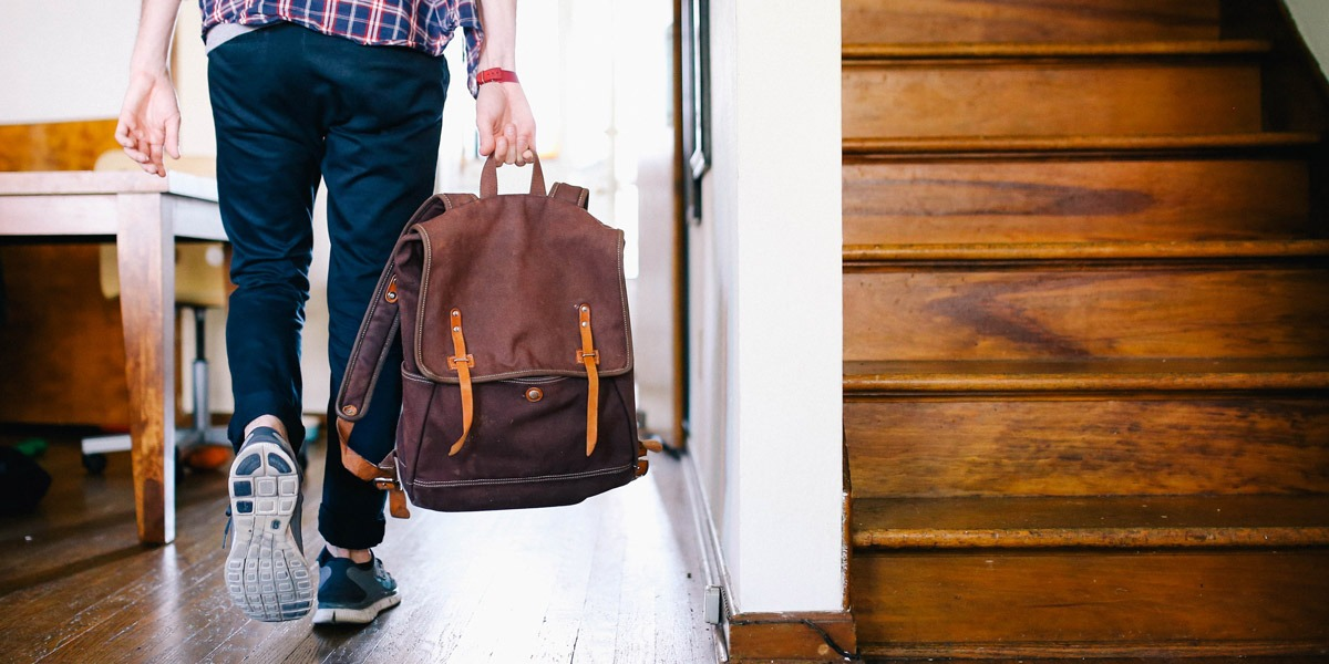 A remote UX designer walking with a packed bag, ready to travel