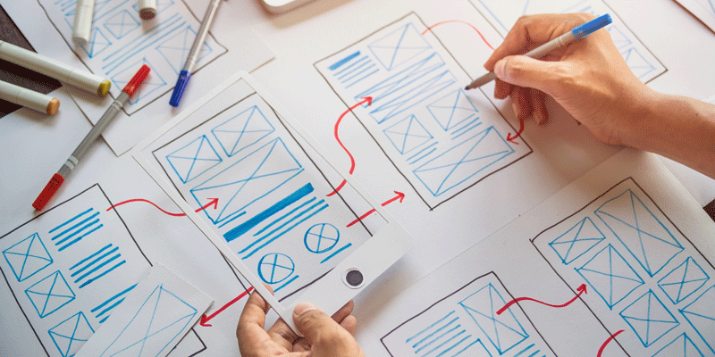 A designer's hands, creating a paper prototype