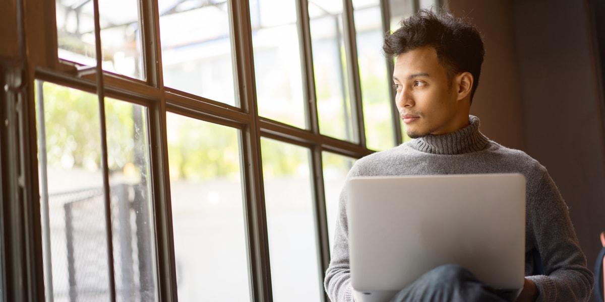 An aspiring designer sitting in a windowsill with their laptop