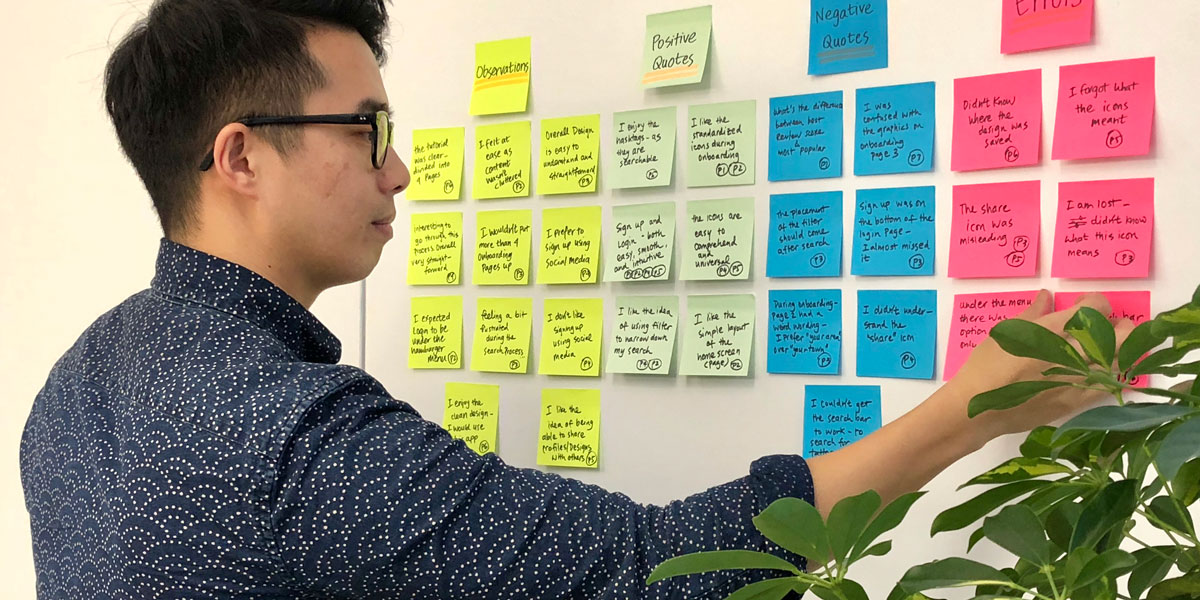 UX designer Ryan Wu standing at a wall covered in sticky notes with research notes