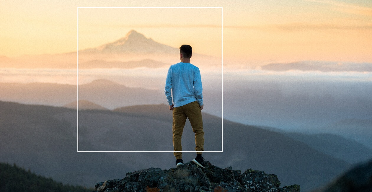 A man stands on a mountain top looking at the horizon.