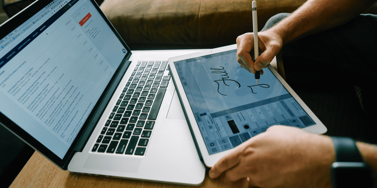 A designer sketching on a tablet with a laptop in front of them