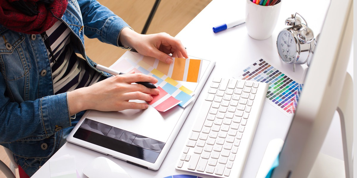 A designer sitting at a desk, looking at color swatches