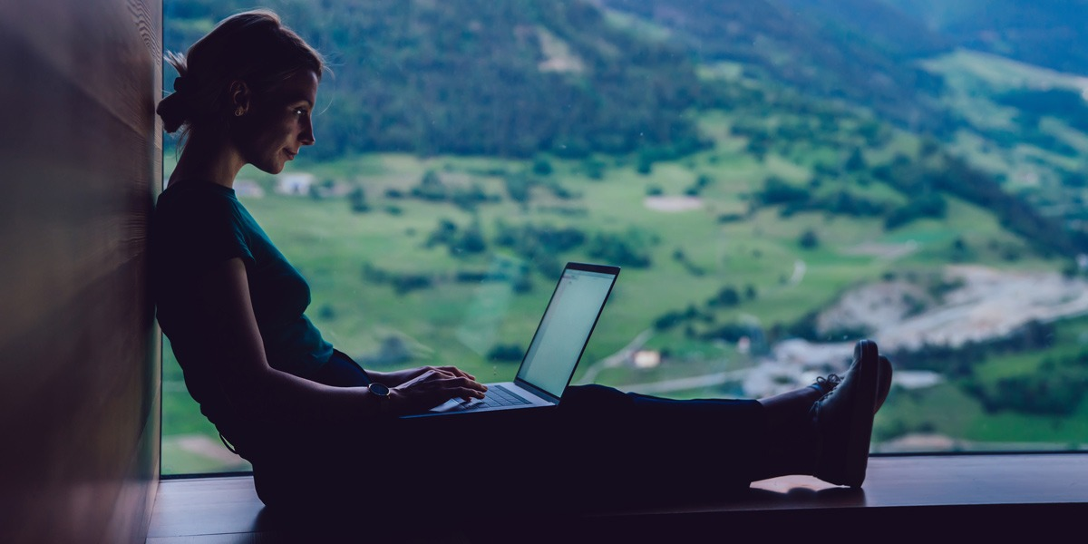 A UI designer in side profile, working on a laptop with a rural backdrop