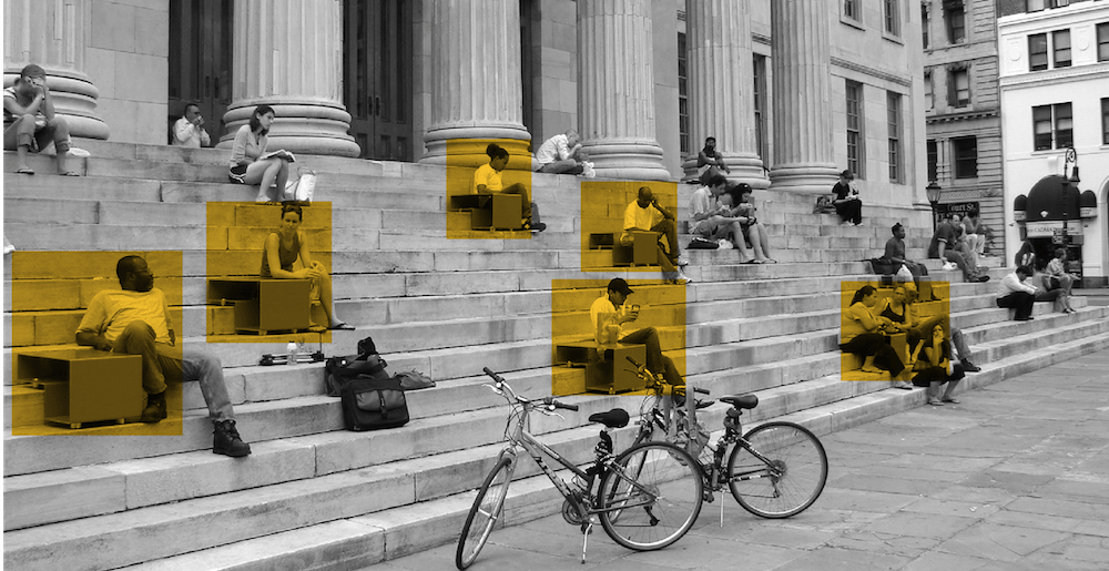 Two bicycles parked at the bottom of a set of marble steps where people are seated