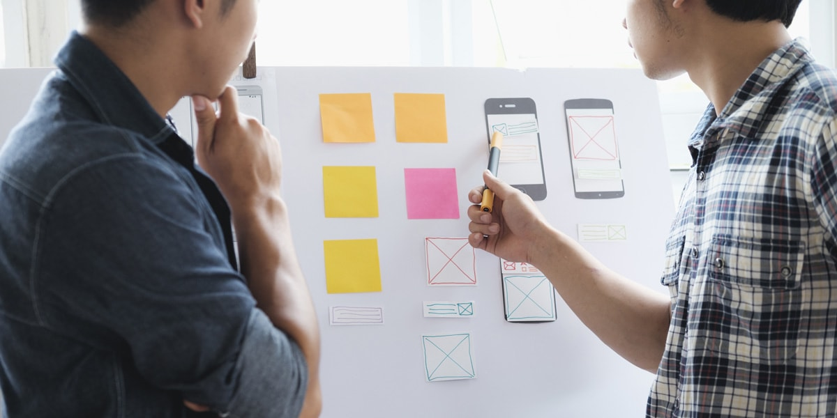 Two designers standing at a whiteboard, looking at notes and prototypes for a project