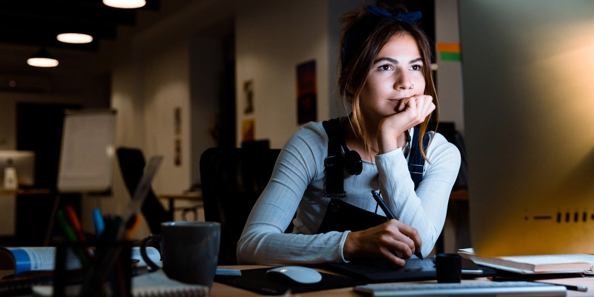 An aspiring designer sitting at a desk in a dark room, writing notes