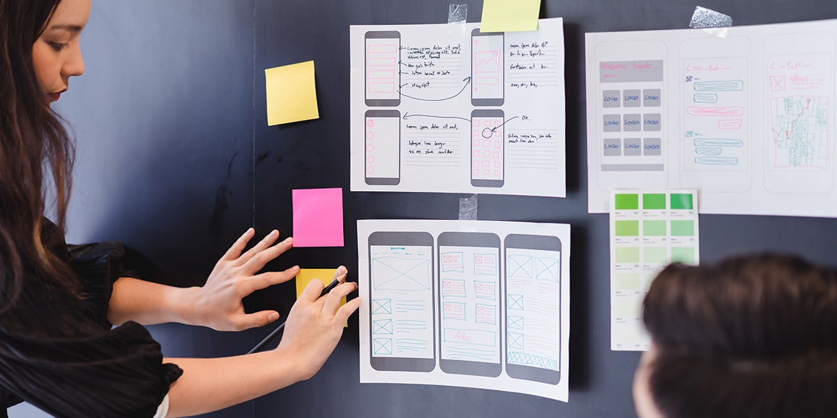 A UX designer looking at a set of wireframes on a wall