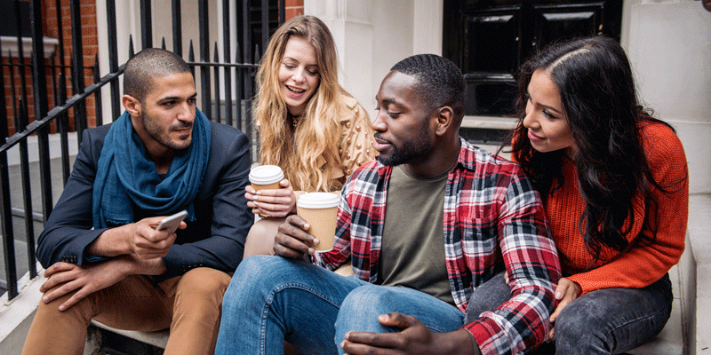 Four people with diverse appearances and backgrounds sitting on some steps, drinking coffee and talking