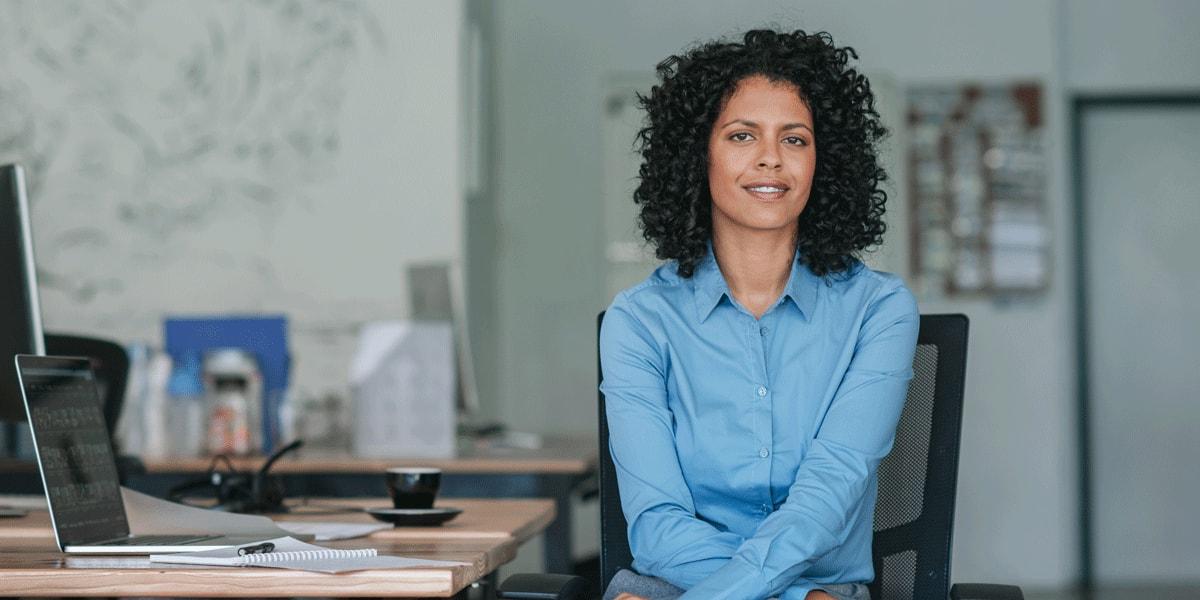 A UX designer sitting at her desk, smiling at the camera