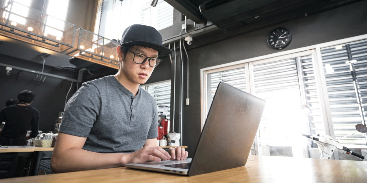 A UX designer sitting at a desk, browsing portfolios on his laptop