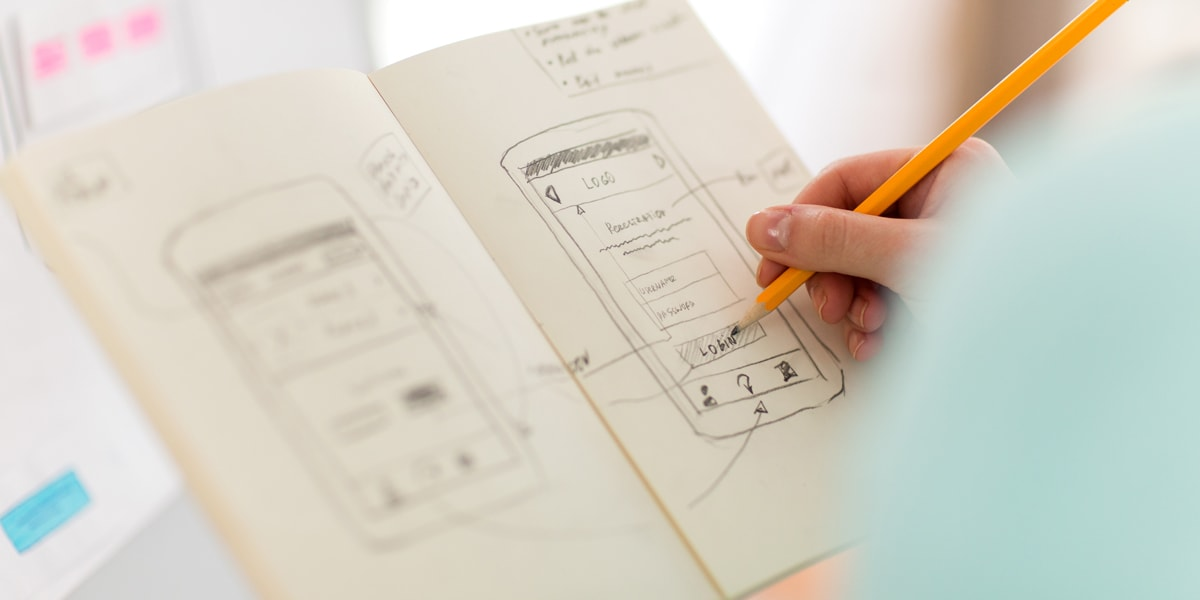 Close-up of a designer's hands, working on a paper prototype for a UX redesign