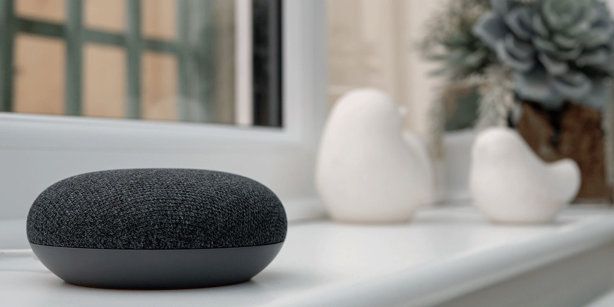 A google VUI device sitting on a tabletop in someone's home