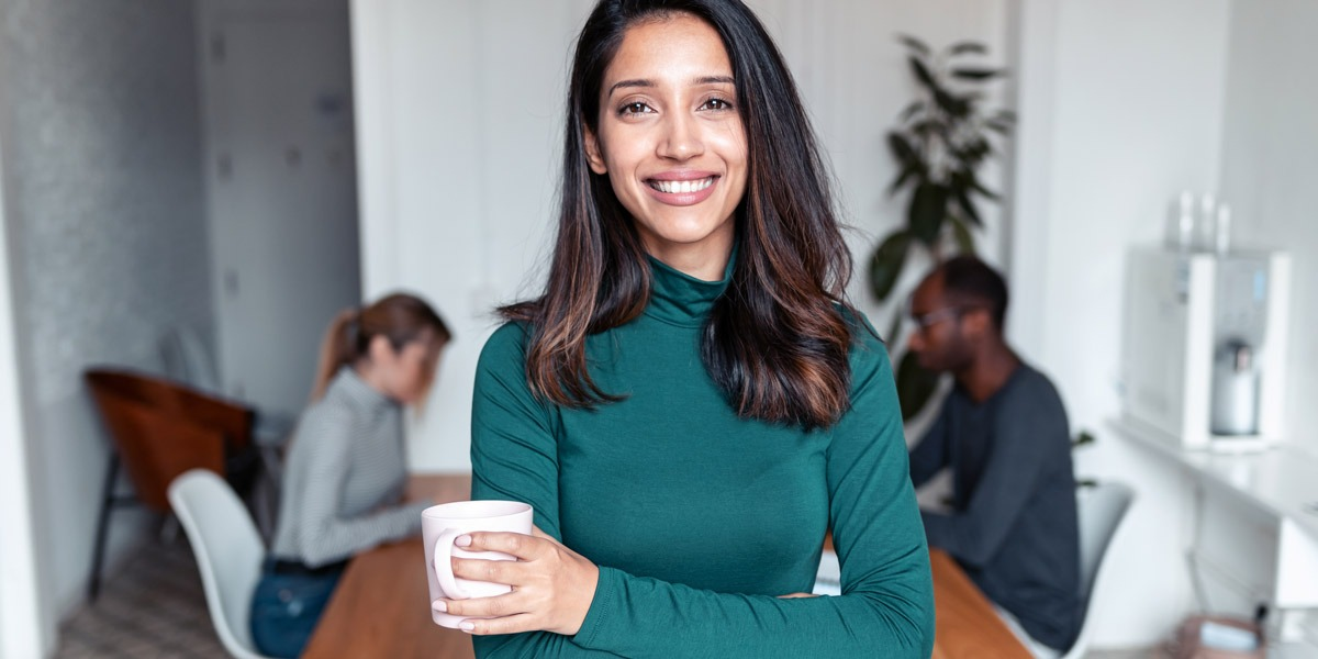 A data analyst holding a cup of coffee, smiling