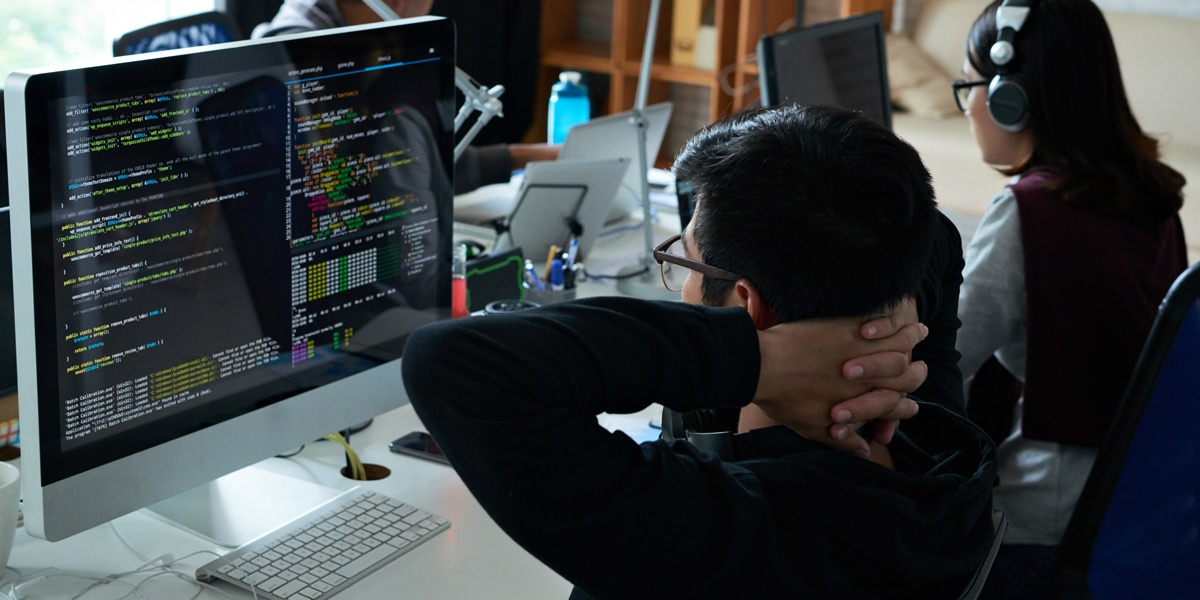 A web developer looking at some code on his computer screen