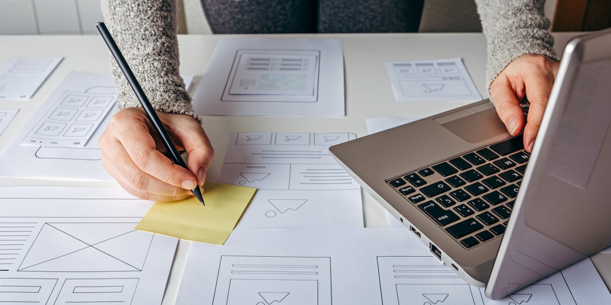A UX designer working at a table with a laptop, writing ideas on a sticky note