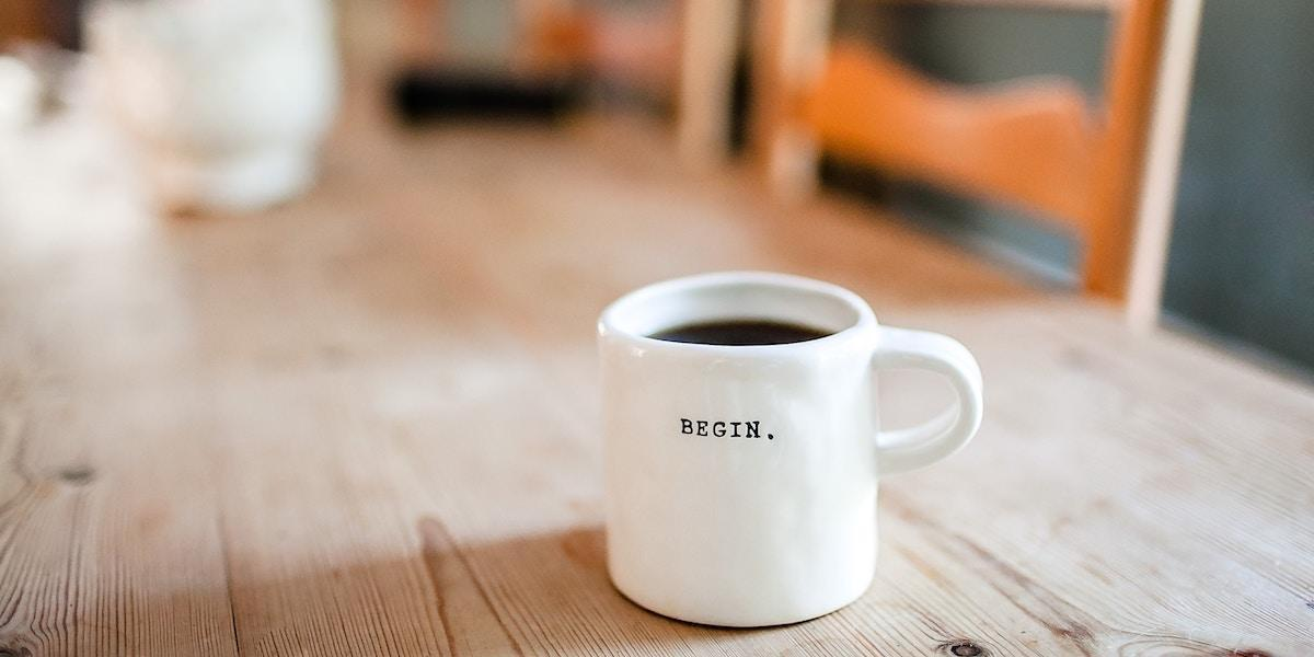 A cup of coffee with the word BEGIN printed on it, sitting on a wooden table