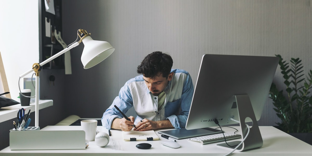 A full-stack web developer working at a computer in an office