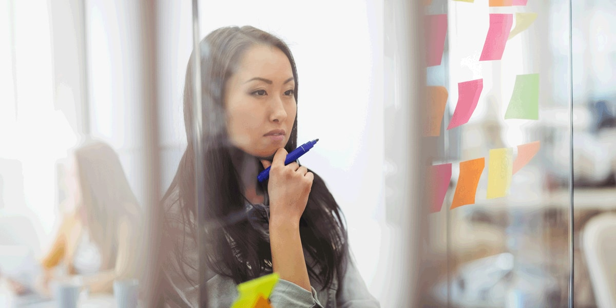 A UX designer standing behind a glass wall covered in sticky notes, deep in thought