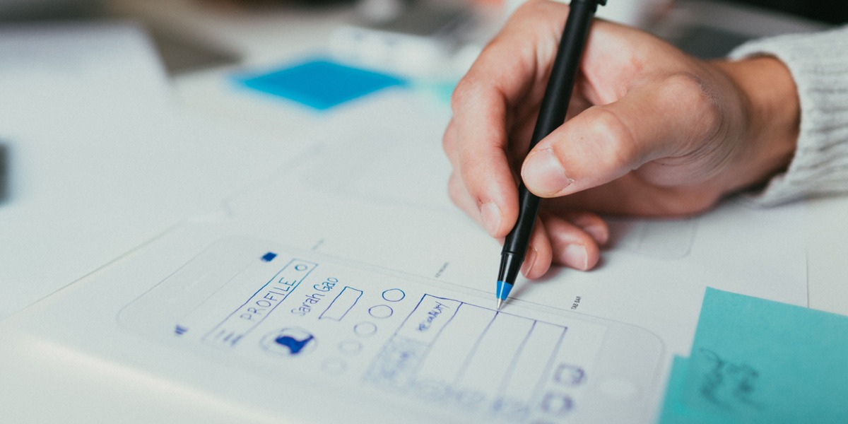 Close-up of a designer's hand working on paper prototypes