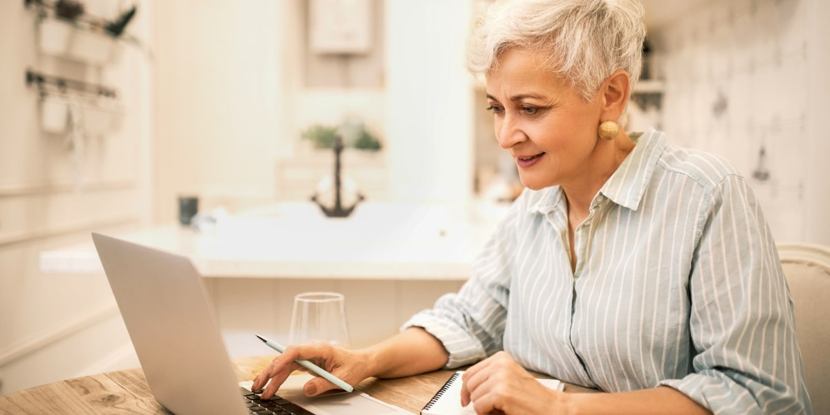 A grey-haired woman sits at her laptop learning to code at home on her laptop.
