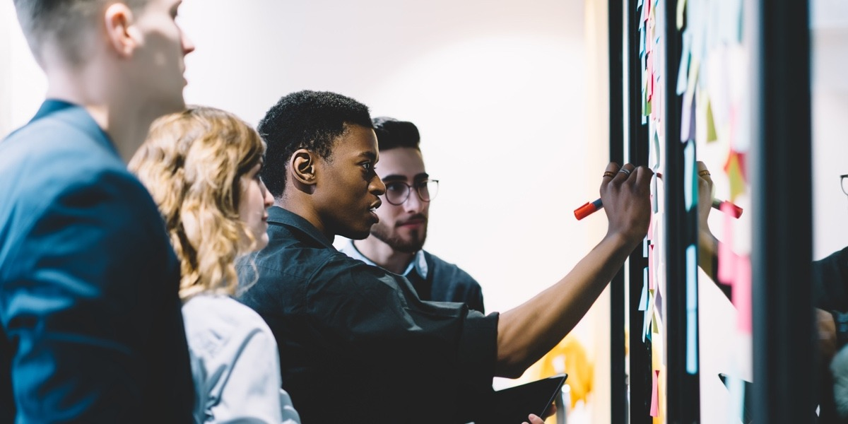 A group of UX professionals gathered around a whiteboard, planning inclusive UX research