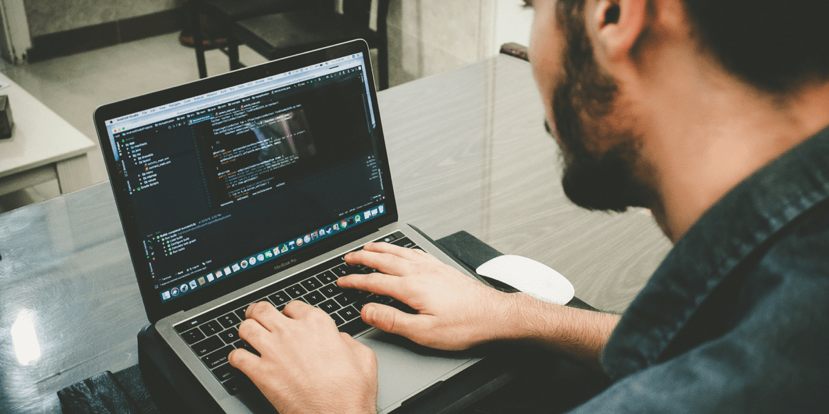 Man sitting at his laptop learning to code in a web development bootcamp