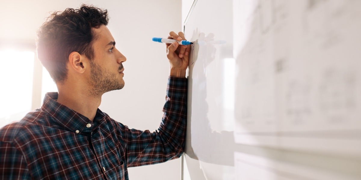 A UX designer drawing ideas out on a whiteboard