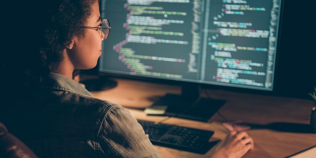 A big data engineer sitting at a desk, looking at a computer screen