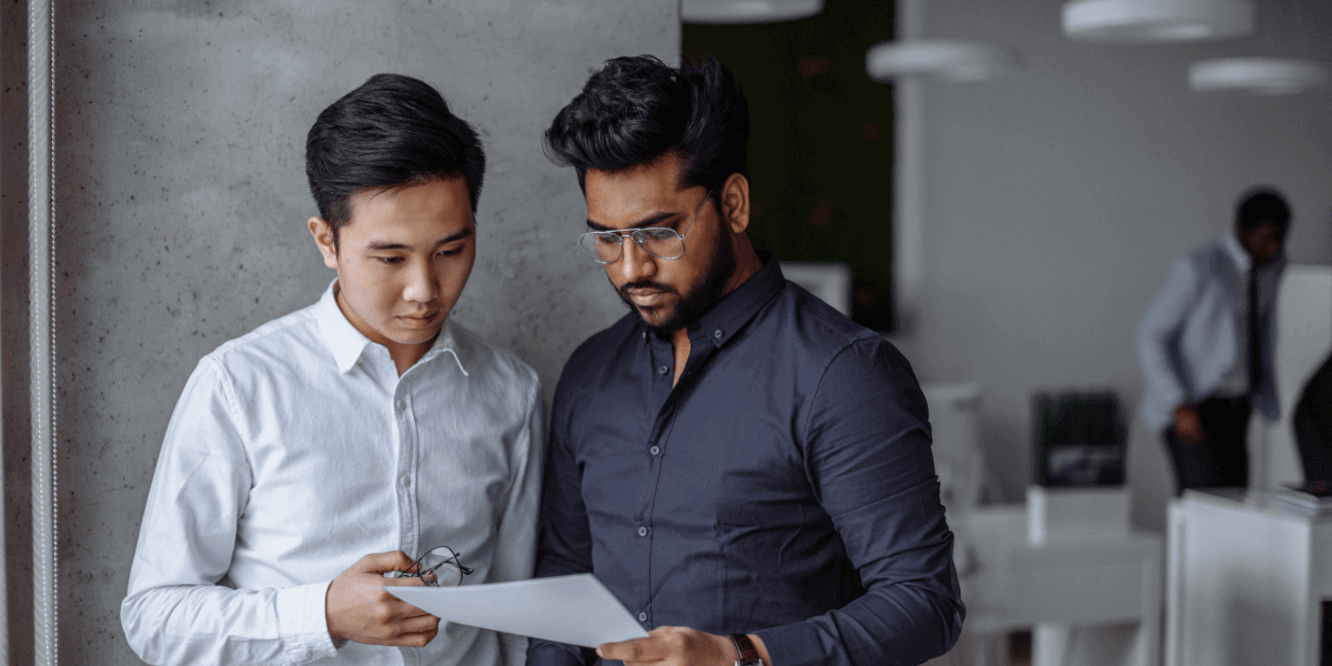 Two financial data scientists standing side by side, looking at a document