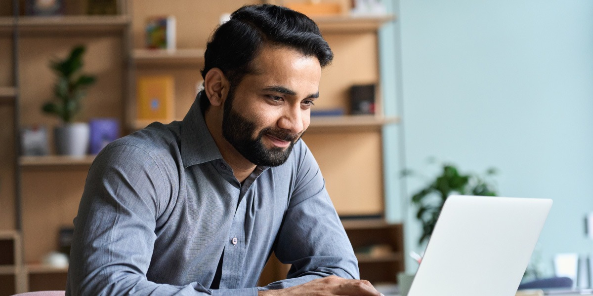 A data analyst in side profile, looking at a laptop screen