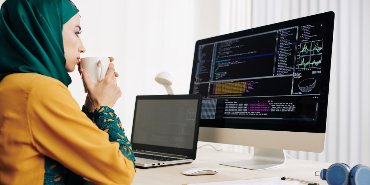 A data analyst in side profile, looking at code on a computer screen