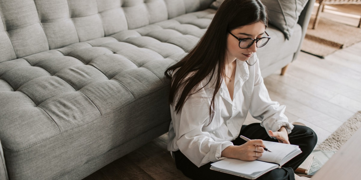 An aspiring designer sitting on the floor of her living room, considering the pros and cons of UX bootcamps