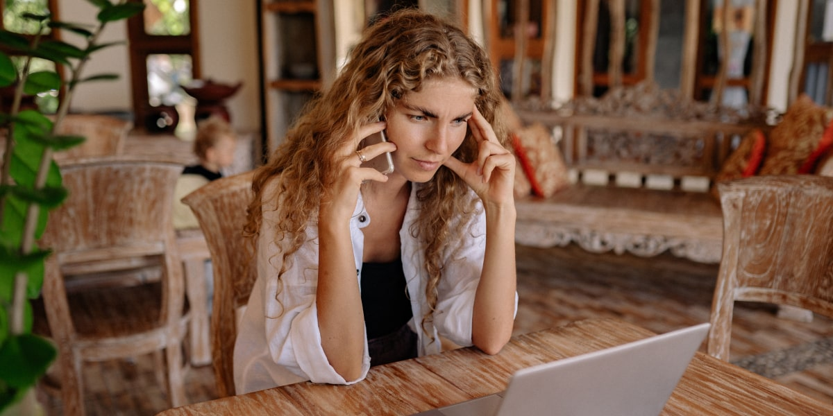 Someone sitting at their dining table, looking at their laptop, and talking on the phone, looking frustrated