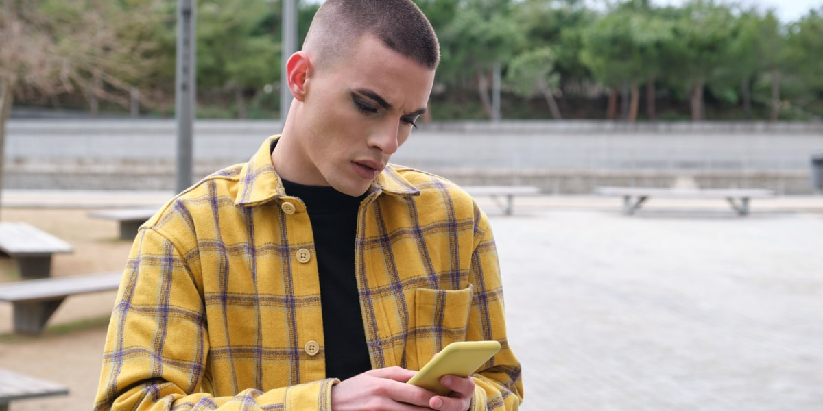A genderqueer person standing in a park, working on their phone