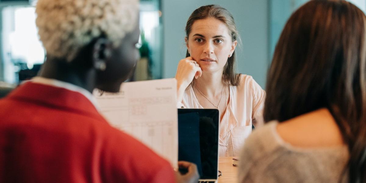 Three women in a web developer interview around a table.