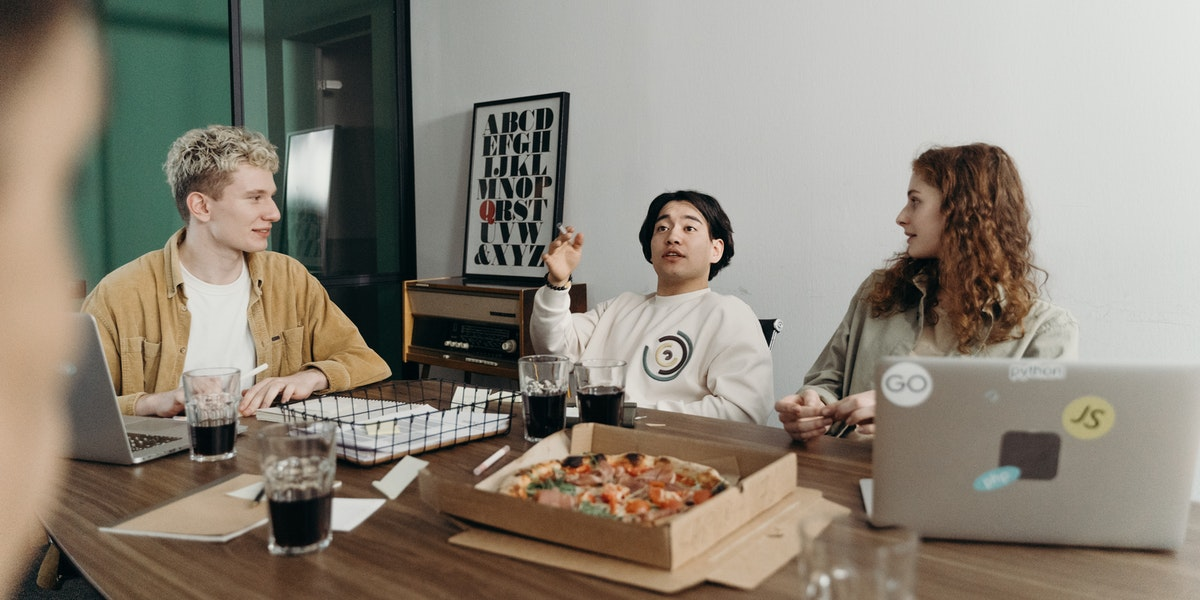 Four web developers sit in an informal meeting in a startup with pizza and coffee.
