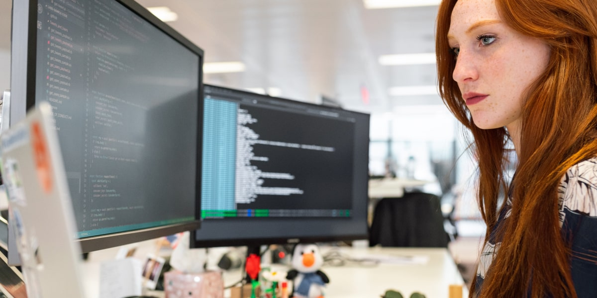 Female web developer sitting at a desk in a startup looking at two screens of code and a laptop