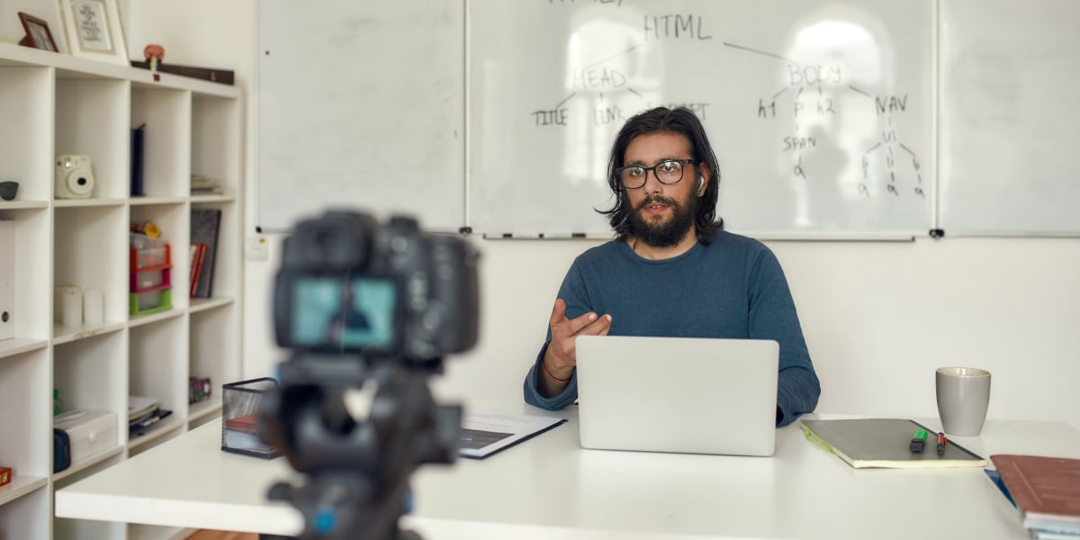 An online coding bootcamp instructor records a video explaining HTML using a camera and laptop.