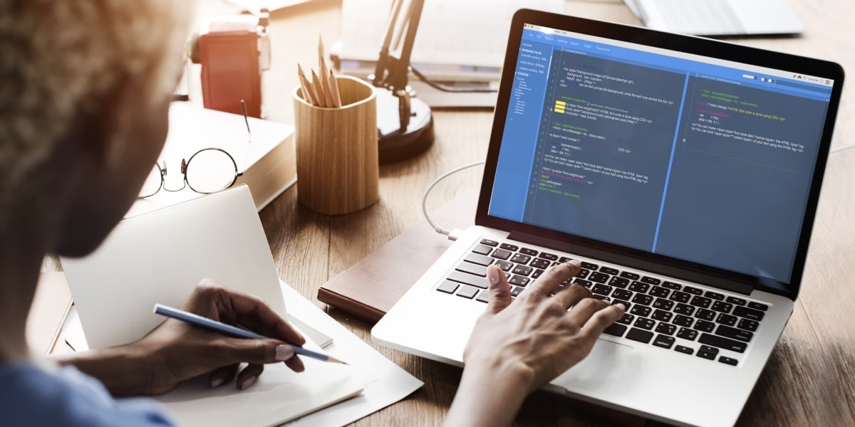 A Bootstrap developer looks at a laptop screen of code.