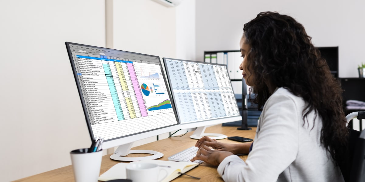 A data analyst looking at two desktop screens