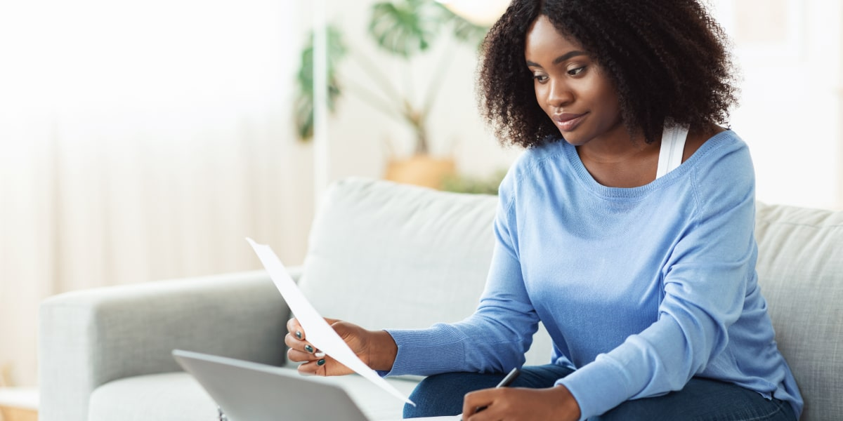 A digital marketing degree student sitting on a sofa, looking at a laptop and holding a sheet of paper