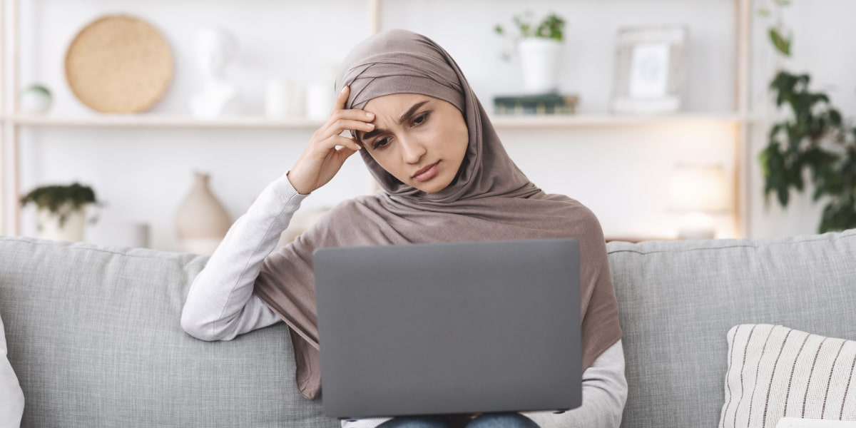 An aspiring digital marketer sitting on a sofa looking at a laptop, weighing up whether to do a digital marketing internship or a course
