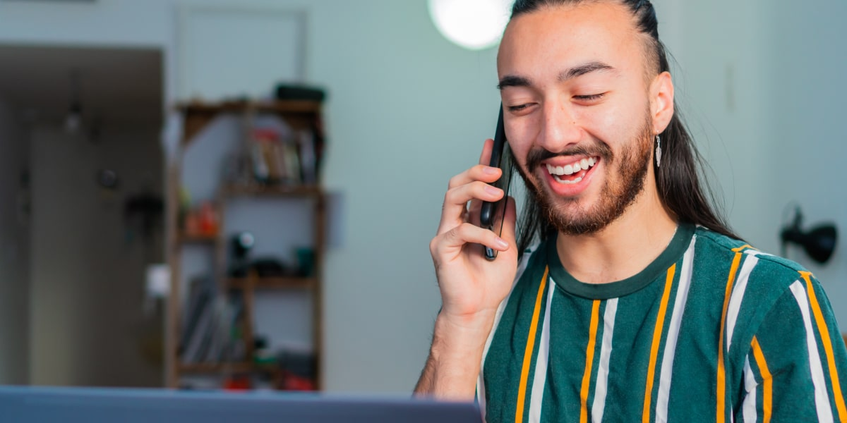 A digital marketing expert speaking into a mobile phone, smiling
