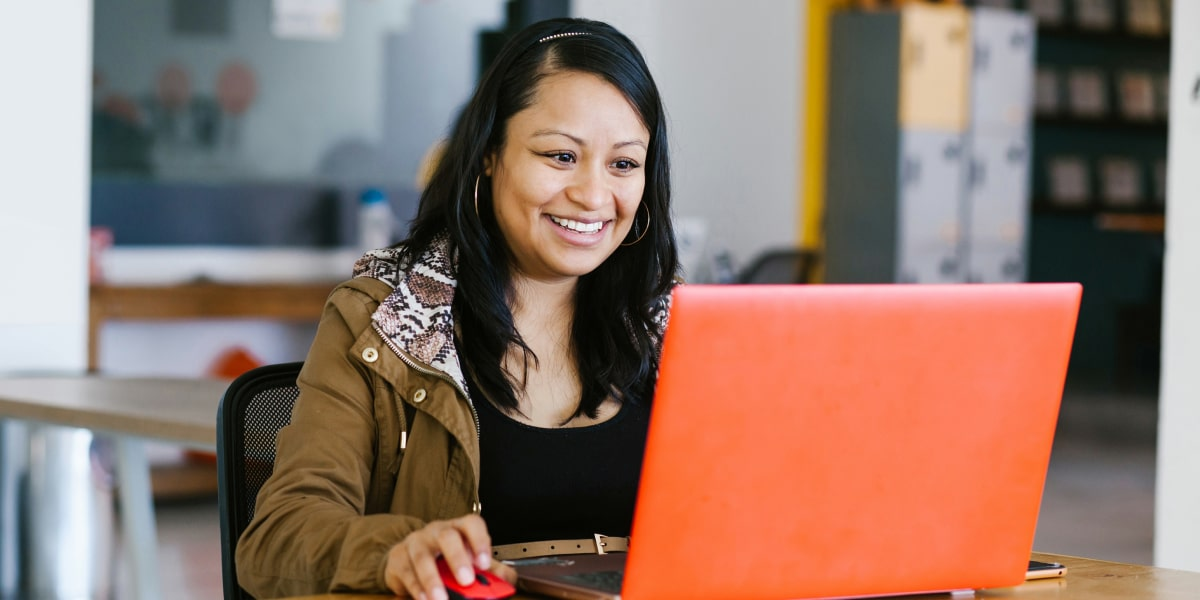 A social media specialist working on a laptop, smiling