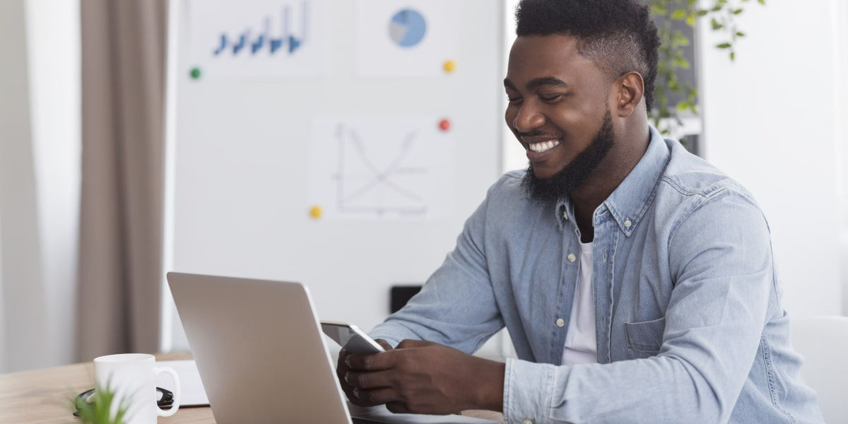 A social media specialist smiling looking at a phone, with a laptop in view