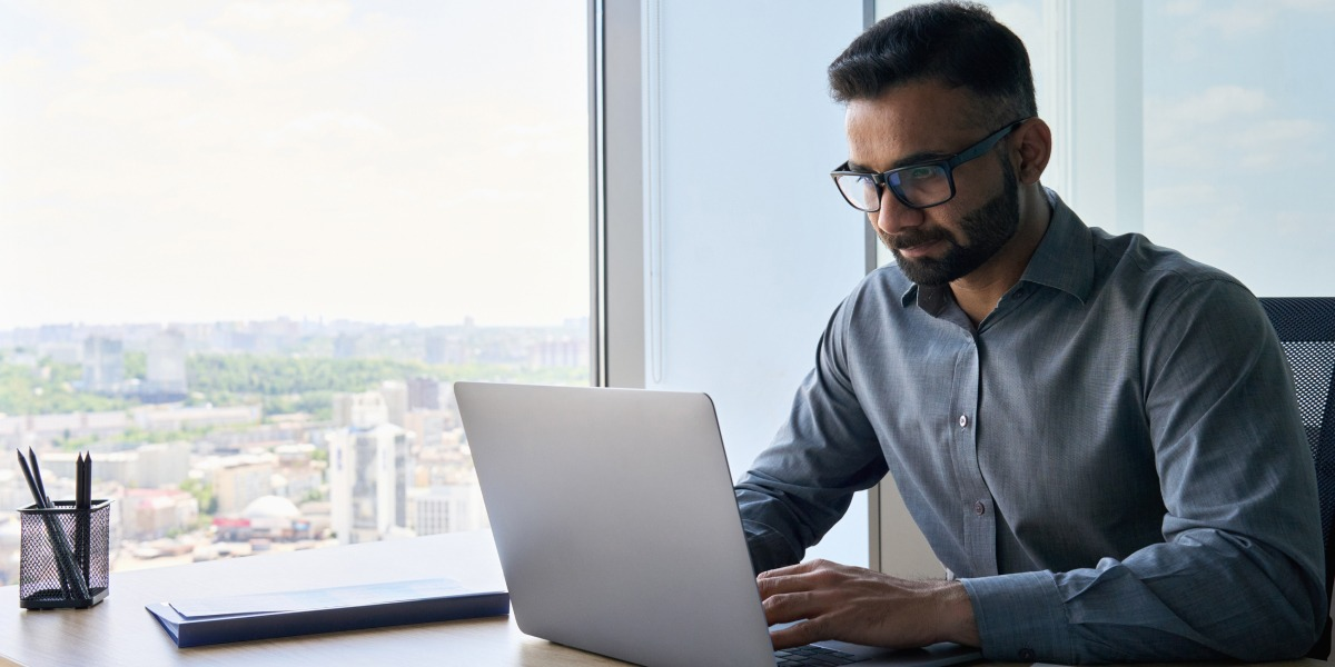 Entry-level data analyst works on a laptop in an office